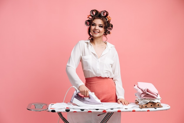 Attraktive junge hausfrau, die saubere kleidung bügelt, während sie hausarbeiten erledigt, lokalisiert auf rosa wand