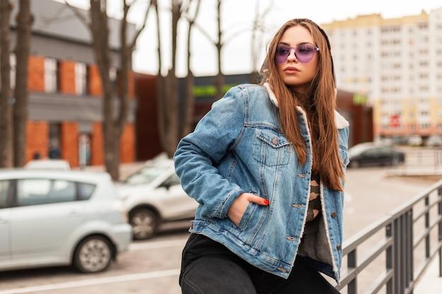 Attraktive junge hipster-frau in stilvoller lila brille in militärkapuze in modischer blauer jeansjacke entspannt sich am frühlingstag auf der straße. schönes städtisches mädchen genießt einen urlaub in der stadt.