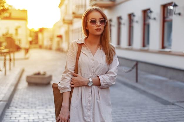 Attraktive junge hipsterfrau in der stilvollen sonnenbrille in einem stilvollen weißen kleid mit einer modischen braunen handtasche geht durch die vintagen straßen der stadt auf einem sonnenuntergangshintergrund. modisches mädchen