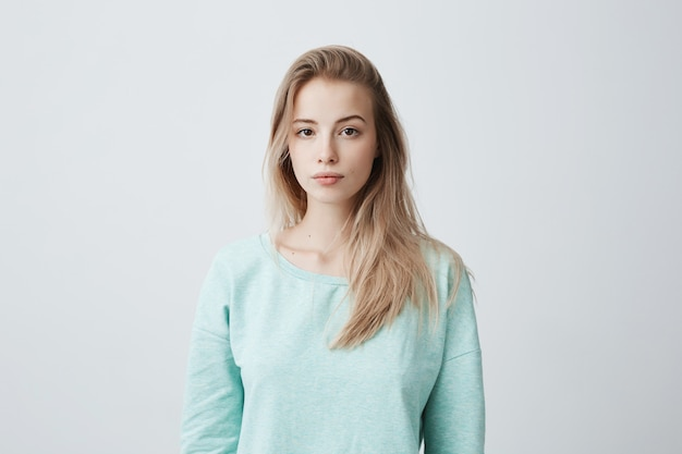 Attraktive junge kaukasische dunkeläugige frau mit langen gefärbten blonden haaren, die gegen graue leere wand posiert, gekleidet in lässigem blauen pullover mit ruhigem gesichtsausdruck.