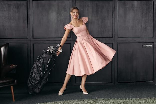 Attraktive junge kaukasische frau mit langen blonden haaren, schönem gesicht, hellen ohrringen im rosa kleid sitzt auf dem großen schwarzen sessel