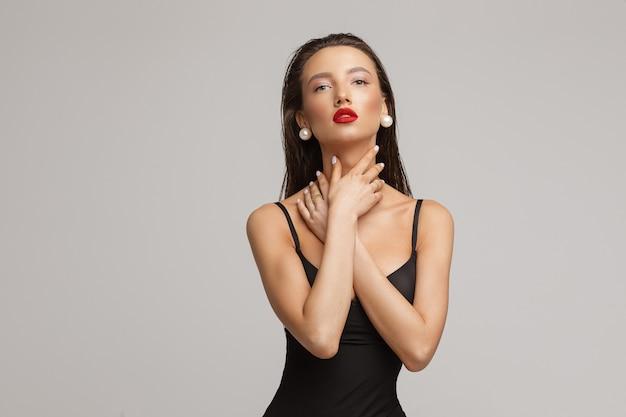 Attraktive junge kaukasische frau mit langen dunklen haaren, schönem make-up, roten lippen im schwarzen badeanzug berührt ihren hals