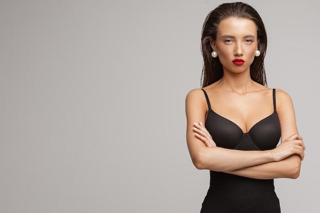 Attraktive junge kaukasische frau mit langen dunklen haaren, schönem make-up, roten lippen im schwarzen badeanzug kreuzte ihre hände auf der brust