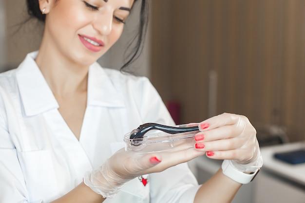 Attraktive junge kosmetikerin, die einen mesoroller in ihren händen hält. schließen sie herauf porträt des dermatologen mit ihrer ausrüstung. spezialist für mesotherapie in der klinik.