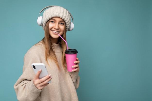 Attraktive junge lächelnde blonde frau trägt beige pullover und beige hut weiße kopfhörer isoliert