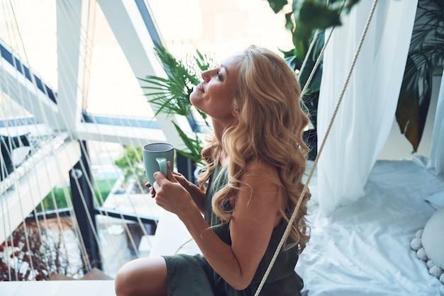 Attraktive junge lächelnde frau, die ein heißes getränk genießt, während sie zu hause auf dem bett sitzt