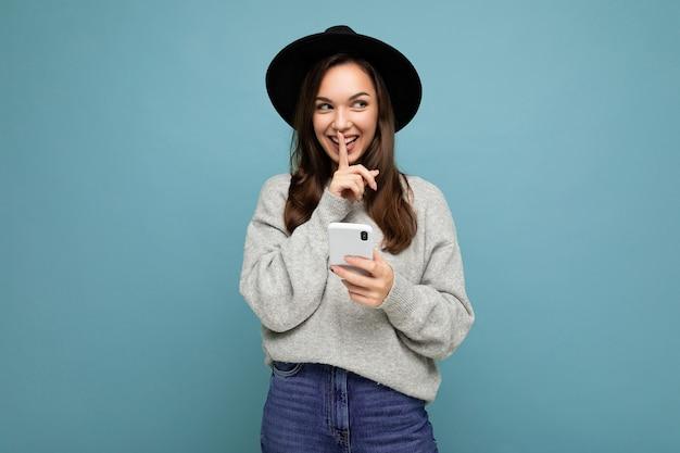 Attraktive junge lächelnde frau mit schwarzem hut und grauem pullover mit smartphone, das zur seite schaut und die shhh-geste einzeln auf hintergrund zeigt.