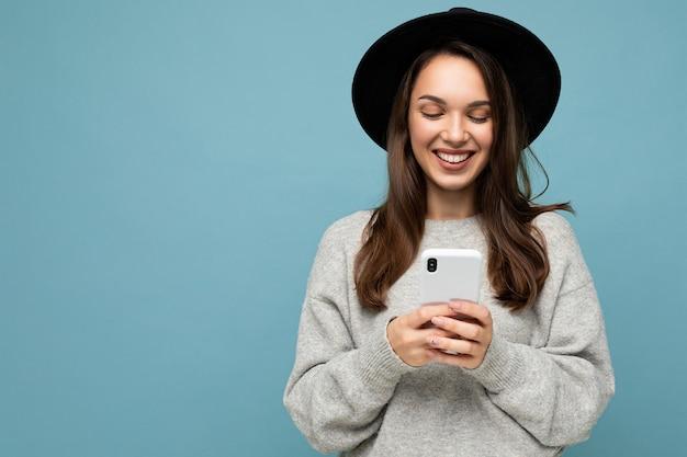Attraktive junge lächelnde frau mit schwarzem hut und grauem pullover mit smartphone, die isoliert auf hintergrund schaut. platz kopieren