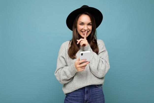 Attraktive junge lächelnde frau mit schwarzem hut und grauem pullover mit smartphone mit blick auf die kamera, die eine shhh-geste einzeln auf dem hintergrund zeigt.