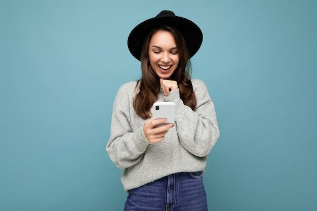 Attraktive junge lächelnde frau mit schwarzem hut und grauem pullover mit smartphone nach unten schauend