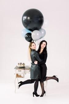 Attraktive junge mädchen in den schwarzen kleidern, die vor weißem weinlese-tisch mit kuchen und martini aufwerfen, die bunte große luftballons auf weißem hintergrund halten. frohes neues jahr, geburtstagsfeier