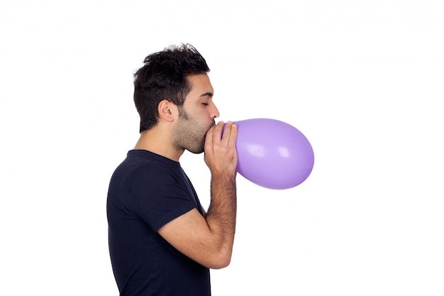 Attraktive junge männer, die einen purpurroten ballon lokalisiert auf weißem hintergrund anschwellen
