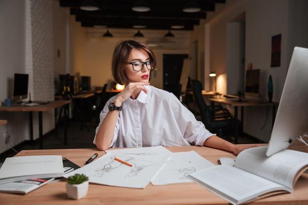 Attraktive junge modedesignerin mit brille, die im büro sitzt und arbeitet