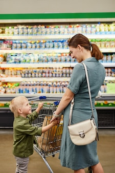 Attraktive junge mutter im blauen kleid, die die hand des sohnes hält und mit ihm spricht, während sie produkte im geschäft kauft