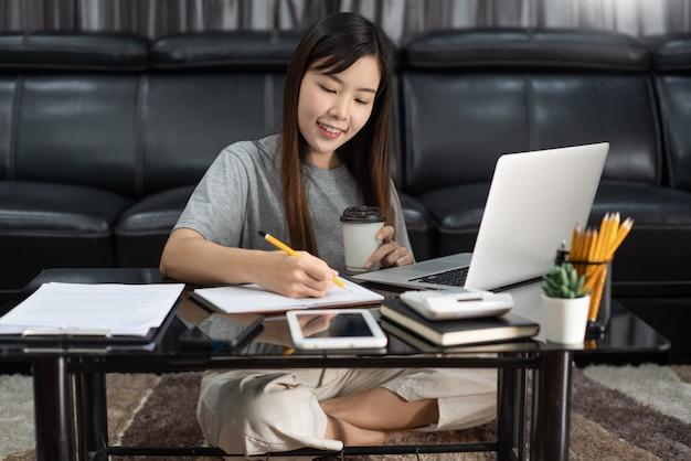 Attraktive junge schöne asiatische frau, die mit laptop und dokument arbeitet, während sie im innenwohnzimmerbüro als freiberufler sitzt, e-coaching arbeitet, entfernt oder von zu hause aus arbeitet.
