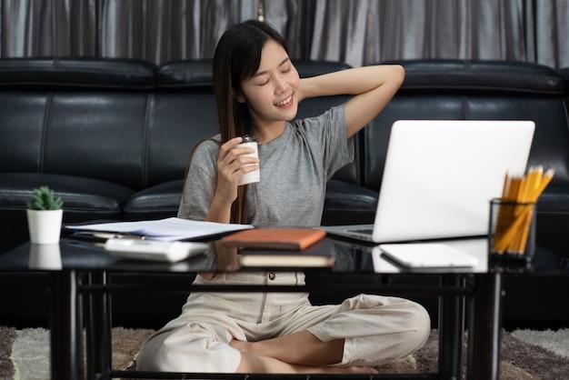 Attraktive junge schöne asiatische frau unternehmerin oder freiberuflerin, die zu hause mit laptop-geschäftsberichten und online-kommunikation auf wohnzimmer-sofa arbeitet, fernzugriffskonzept.