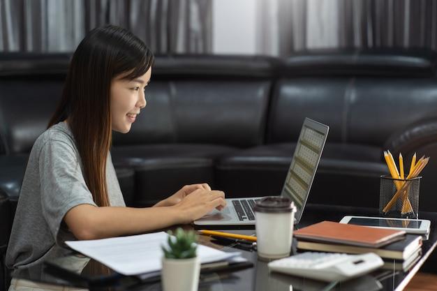 Attraktive junge schöne asiatische frau unternehmerin oder freiberuflerin, die zu hause mit laptop-geschäftsberichten und online-kommunikation auf wohnzimmer-sofa arbeitet und fernzugriffskonzept arbeitet.