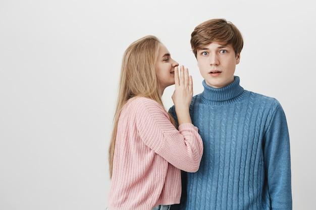 Attraktive junge schöne frau, die geheimnisse teilt oder klatsch in ihren freund flüstert