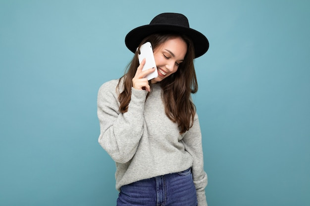 Attraktive junge schüchterne lächelnde frau, die schwarzen hut und grauen pullover hält smartphone hält, das lokal auf hintergrund schaut.