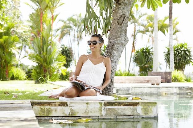 Attraktive junge schwangere frau, die stilvolle sonnenbrille und sommerkleid trägt, die freizeit im freien verbringen, urlaub im kurort im tropischen land genießend, auf gras nahe schwimmbad sitzend