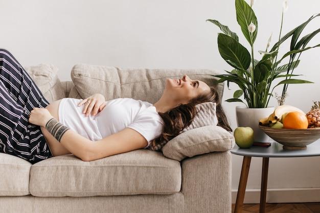 Attraktive junge schwangere frau mit tätowierungen auf der hand lachend