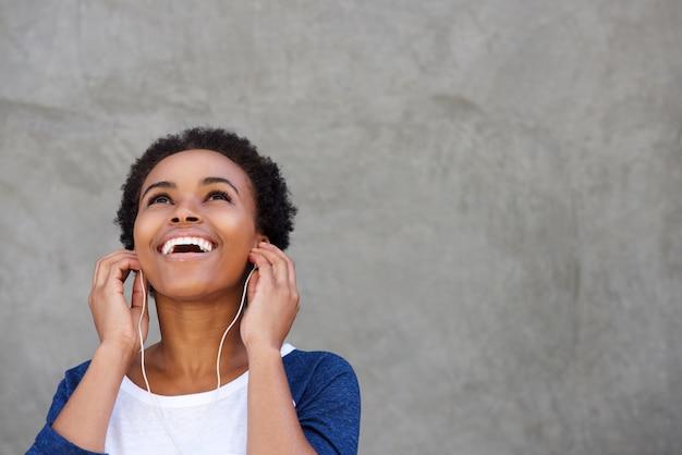Attraktive junge schwarze frau, die mit kopfhörern lächelt