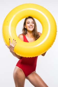 Attraktive junge sexy schöne frau im roten badeanzug hält runde gelbe luftmatratze lokalisiert auf weißem hintergrund