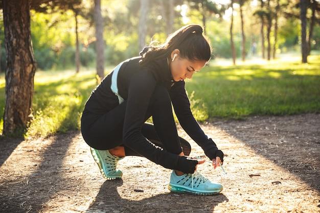 Attraktive junge sportfrau, die schnürsenkel am park bindet