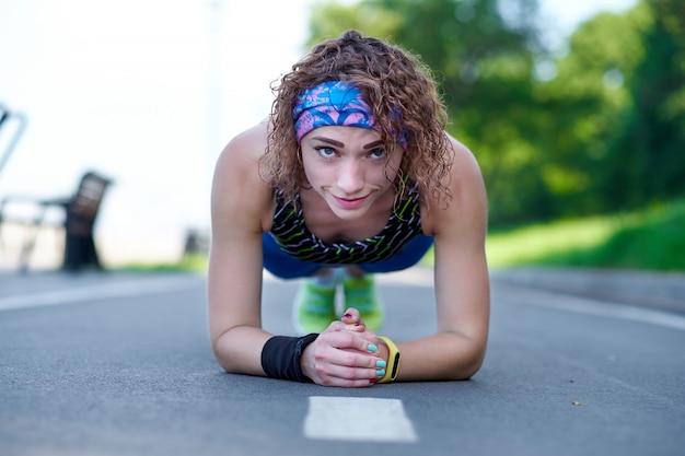 Attraktive junge sportlerin, die plankenübung auf rennbahn tut