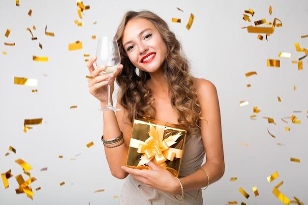 Attraktive junge stilvolle frau, die neues jahr feiert, geschenke in der schachtel hält, goldenes konfetti fliegt, glücklich lächelnd, partykleid tragend
