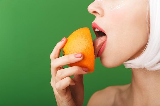 Attraktive junge topless frau, die kurzes weißes haar trägt, das isoliert steht und geschnittene orange isst