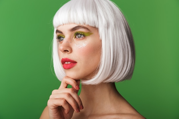 Attraktive junge topless frau, die kurzes weißes haar trägt, das isoliert steht und wegschaut