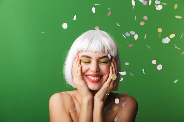 Attraktive junge topless frau, die kurzes weißes haar trägt, das unter konfettiregen isoliert steht