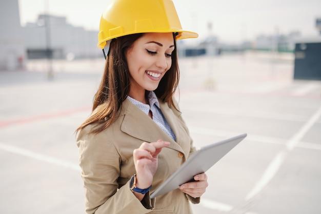 Attraktive kaukasische architektin gekleidet schick lässig und mit helm auf kopf mit tablette beim stehen auf der baustelle.