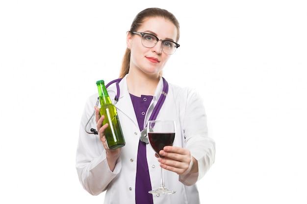 Attraktive kaukasische brunetteärztin, die im büro mit flasche und glas wein in ihren händen steht