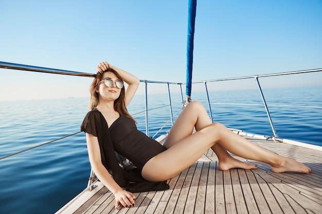 Attraktive kaukasische frau im urlaub, sonnenbaden auf privater yacht, die hand auf kopf hält, erfreut und entspannt.