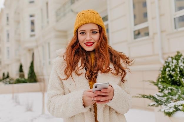 Attraktive kaukasische frau in der strickmütze, die telefon hält. außenfoto des inspirierten ingwermädchens trägt weißen mantel.