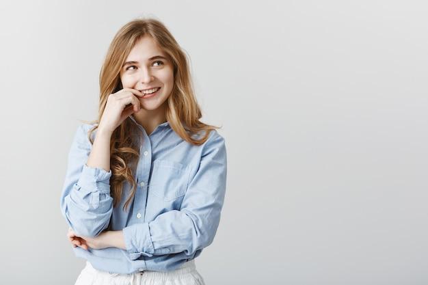 Attraktive kaukasische frau mit blondem haar, blick auf die obere rechte ecke, neugierig lächelnd und lippen berührend