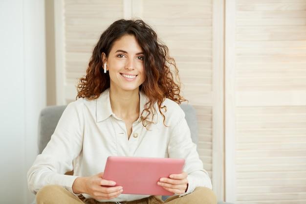 Attraktive kaukasische frau mit dem gelockten haar, das weißes hemd hält rosa tablet-computer hält