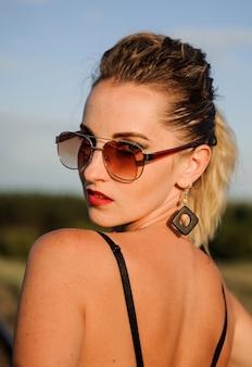 Attraktive kaukasische frau mit sonnenbrille untersucht die kamera und schaut über ihre schulter.