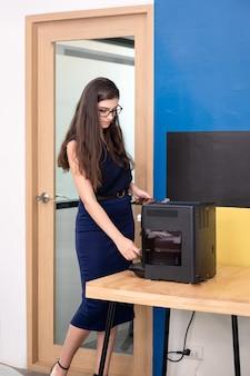 Attraktive kaukasische geschäftsfrau, die mit heißem kaffee von kaffeemaschine im büro steht