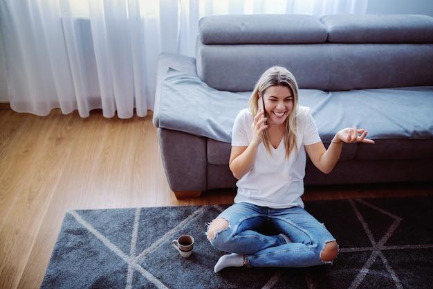 Attraktive kaukasische junge blonde frau, die auf dem boden im wohnzimmer mit gekreuzten beinen sitzt und auf dem smartphone spricht. neben ihr steht eine tasse mit frischem kaffee.