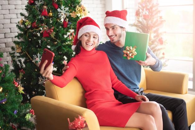 Attraktive kaukasische paare der liebe feiern weihnachten im haus