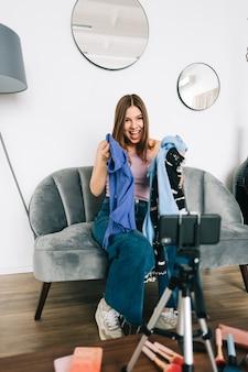 Attraktive kaukasische video-bloggerin für junge frauen, die über ihren blog in den sozialen medien neue kleidung zeigt