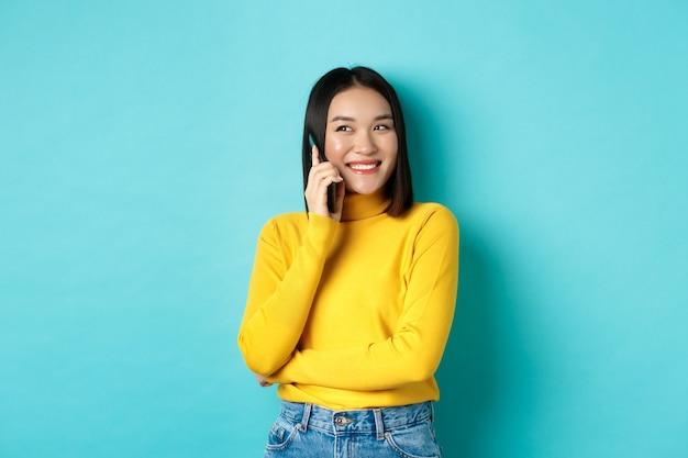 Attraktive koreanische frau im gelben pullover, die sich unterhalten und lächelt, mit dem handy spricht, nach links auf den kopierraum schaut, auf blauem hintergrund steht