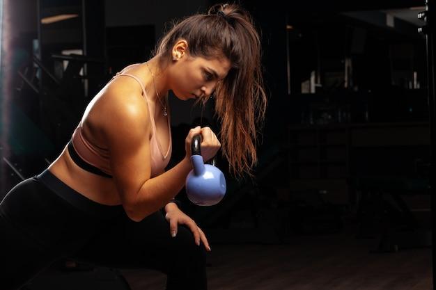 Attraktive kurvige junge frau, die mit hantel in einem fitnessstudio arbeitet