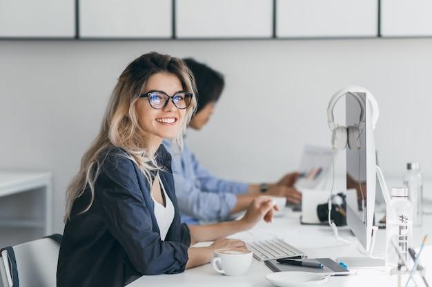Attraktive lachende freiberufliche frau, die mit tasse kaffee an ihrem arbeitsplatz aufwirft. chinesischer student im blauen hemd arbeitet mit dokument im campus mit blondem freund in der brille.