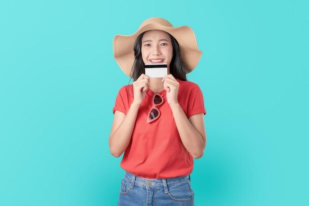 Attraktive lächeln asiatin, die kreditkartenzahlung auf blau hält.
