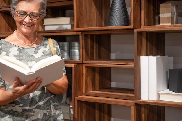 Attraktive lächelnde ältere frau, die das lesen eines buches genießt. bücherregal aus holz hinter ihr