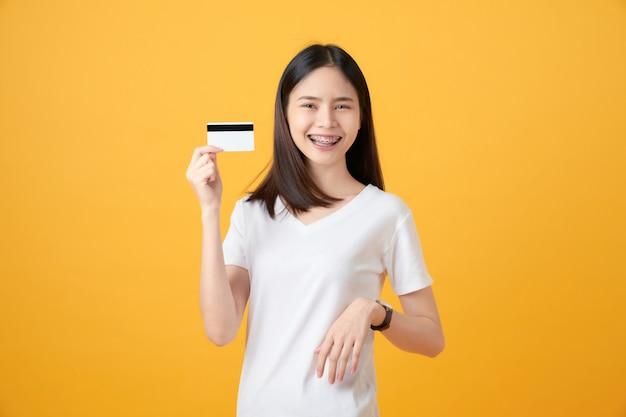 Attraktive lächelnde asiatische frau, die kreditkartenzahlung auf gelber wand hält